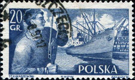 postmail: POLAND - CIRCA 1955  A stamp printed in Poland shows a sailor and freighter  Pokoj  in dock, circa 1955