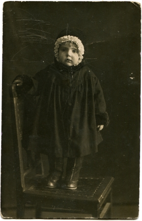 a frill: portrait of little girl in a dark coat and a hat with a white frill, standing on a chair, Lugansk, Ukraine, 1924 Editorial