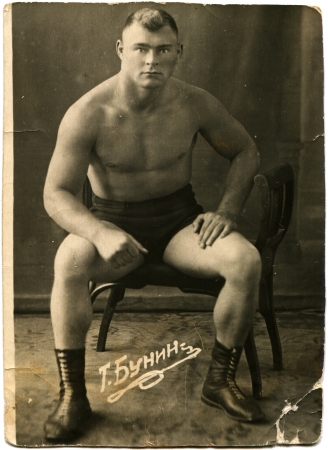 USSR - CIRCA 1930s  Studio portrait of a fighter, sitting on a chair, circa 1930s, Russian text - T Bunin