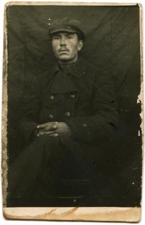 hombre sentado: URSS - CIRCA 1925 Retrato de un hombre sentado en un saco y gorra, circa 1925