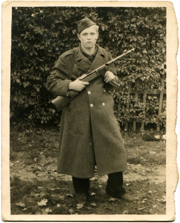 unmarked: GERMANY - CIRCA 1940s  Reproduction of picture made in Germany shows young man in the form of a German soldier, unmarked with a gun, sirca end of 1940s