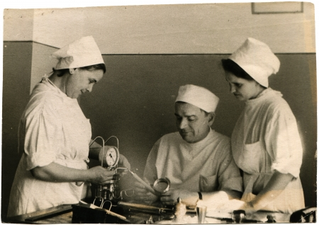 USSR - CIRCA 1960s  Reproduction of photo was take in USSR shows a doctor and two nurses with medical device, about 1960s Editorial