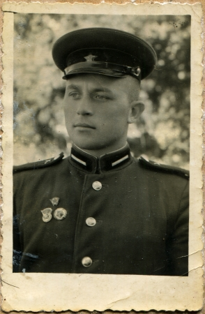 corporal: USSR - CIRCA 1958  Postcard shows Corporal of the Soviet Army, on his chest badges of Komsomol and two of sports, the USSR, 1958 Editorial