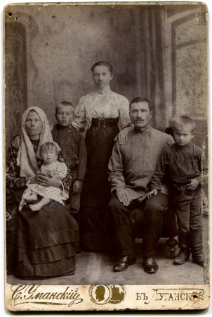 russian man: RUSSIA - CIRCA end of the XIX - the beginning of XX century  An antique photo shows family of the worker Lugansk, Russian Empire, now UkraineRussian text  Umanskiy  name of photographer , Lugansk