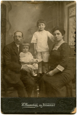 family memories: RUSSIA - CIRCA end of the XIX - the beginning of XX century  An antique photo shows family with two children, Lugansk, Russian EmpireRussian text  Umanskiy  name of photographer , Lugansk