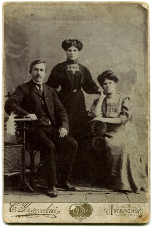 xx century: RUSSIA - CIRCA end of the XIX - the beginning of XX century  An antique photo shows man sitting at the table with two women, Lugansk, Russian Empire, UkraineRussian text  Umanskiy  name of photographer , Lugansk