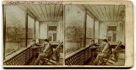 quandary: RUSSIA - CIRCA 1913  An antique photo shows stereo, a man with a boy playing checkers on the porch at home, the Russian Empire, 1913Russian text  quandary