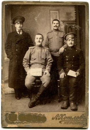 army man: RUSSIA - CIRCA period of World War I  An antique photo shows three soldiers and a student, Kherson, Russian Empire, now UkraineRussian text  Kolov  photographer , Kherson