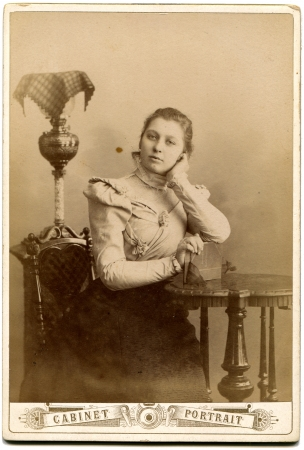 xx century: RUSSIA - CIRCA  the end of 19 - early 20century  An antique photo shows girl sitting near a table, based on the book, the Russian Empire