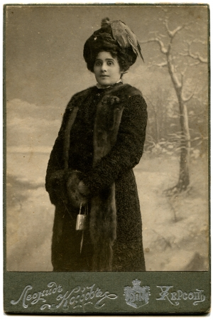 fur coat: RUSSIA - CIRCA  the end of 19 - early 20 century  An antique photo shows woman in a fur coat and hat with a clutch in their hands, Kherson, Russian EmpireRussian text  Leonid Koff  photographer , Kherson