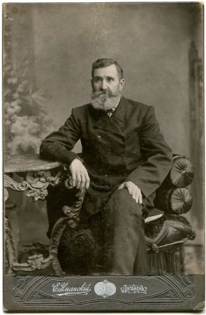 RUSSIA - CIRCA the end of 19 - early 20 century An antique photo shows man in a business suit with a mustache and beard, sitting in a chair at the table, Lugansk, Russian Empire, now UkraineRussian text Umanskiy photographer , Lugansk Editorial