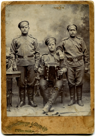 RUSSIA - CIRCA  1914 - 1917  An antique photo shows Three soldiers with an accordion, Saratov, Russian Empire