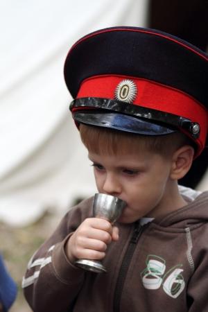 cossack: STANITSA LUGANSKAYA, UKRAINE - SEPTEMBER, 8, 2012  boy in uniform cap of Don Cossack drinking from metallic cup, International Cossack festival, Stanitsa Luganskaya, Ukraine, September 8, 2012