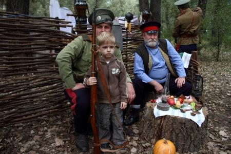cossack: STANITSA LUGANSKAYA, UKRAINE - SEPTEMBER, 8, 2012  little boy with gun with two Don Cosacks, International Cossack festival, Stanitsa Luganskaya, Ukraine, September 8, 2012