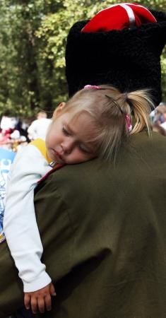 cossack: STANITSA LUGANSKAYA, UKRAINE - SEPTEMBER, 8, 2012  little girl sleeping on the shoulder of her father, the Cossack, International Cossack festival, Stanitsa Luganskaya, Ukraine, September 8, 2012