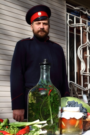 lugansk: LUGANSK - OCT 14  Cossack is standing near the table with vodka infusion, celebration of the Protection of the Mother of God, Lugansk, Ukraine, October 14, 2012 Editorial