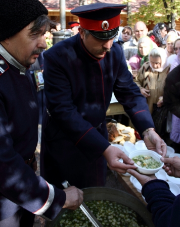 luhansk:  LUGANSK - OCT 14  Don Cossack gives gruel to treat parishioners, celebration of the Protection of the Mother of God, Lugansk, Ukraine, October 14, 2012