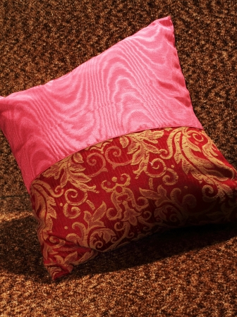 Red decorative pillow on a brown chair photo