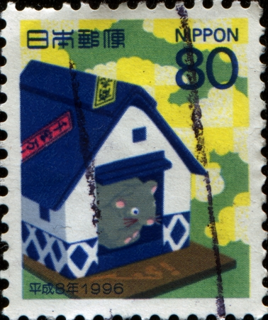 JAPAN - CIRCA 1996: A New Year's Greetings stamp printed in Japan shows Satsuma papier-mache rat in rice store, circa 1996