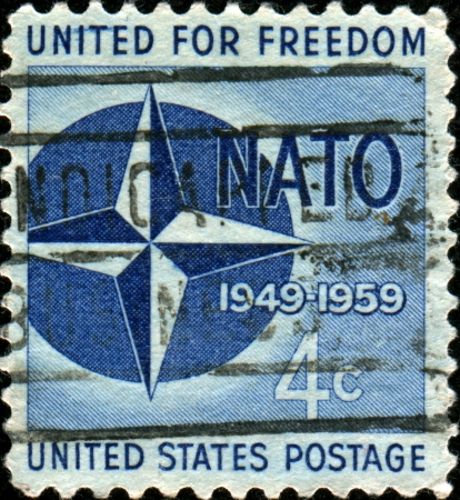 north atlantic treaty organization:  UNITED STATES OF AMERICA - CIRCA 1959: A stamp printed in the United States of America shows NATO Emblem, 10th anniversary of North Atlantic Treaty Organization, circa 1959