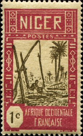 counterpoise:  NIGER - CIRCA 1926: A stamp printed in Niger shows Drawing Water from Well, circa 1926 Editorial
