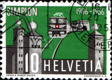 SWITZERLAND - CIRCA 1956  A stamp printed in Switzerland issued for the 50th anniversary of opening of Simplon Tunnel shows electric train emerging from the tunnel and Stockalper Palace, circa 1956