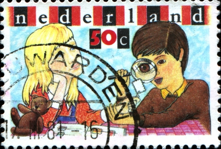 philately:  NETHERLANDS - CIRCA 1980  A stamp printed in Netherlands shows Boy and Girl Inspecting Stamp, Youth Philately, circa 1980