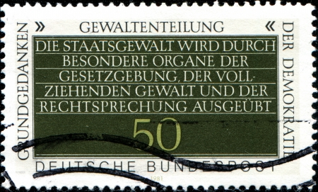 interchangeably: GERMANY - CIRCA 1981  A stamp printed in German Federal Republic showstext -  separation of powers, often imprecisely used interchangeably with the trias politica principle, circa 1981 Editorial
