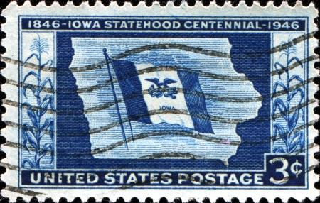 centennial: USA - CIRCA 19 Un timbro stampato negli Stati Uniti d'America mostra Mappa di Stato di bandiera, con iscrizione Iowa Statehood Centennial, circa 1946
