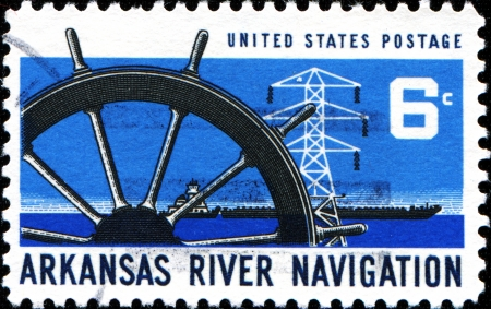 USA - CIRCA 1968  A stamp printed in United States of America shows dedicated to Arkansas river navigation, shows ship wheel, power transmission tower and barge, circa 1968