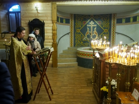carry out: Ukraine, Lugansk - January 7, 2014 Orthodox Christians from Lugansk celebrated Christmas in the Baptistary of the Our Lady of Tenderness temple  Priests carry out a Christmas public prayer