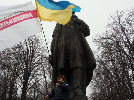 lugansk: UKRAINE, LUGANSK - JANUARY 5, 2014  Opposition rally in Lugansk  Activist with two flags near monument to Taras Shevchenko Editorial