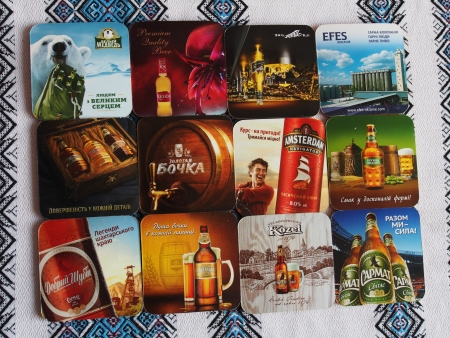 meets: UKRAINE, LUGANSK - JANUARY 26, 2014: Modern beer mats. Beer lovers club meets monthly symbols in various pubs town. Men bring to meetings beer mats, labels and stoppers. They tasts new beers, discuss them and changing souvenirs.