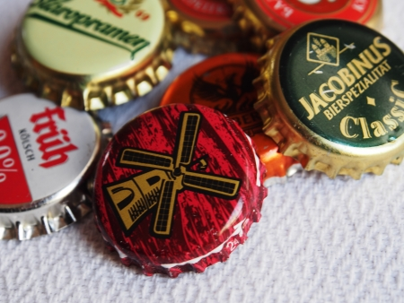 UKRAINE, LUGANSK - JANUARY 26, 2014: Beer bottle caps.   Beer lovers club meets monthly symbols in various pubs town. Men bring to meetings beer mats, labels and stoppers. They tasts new beers, discuss them and changing souvenirs.