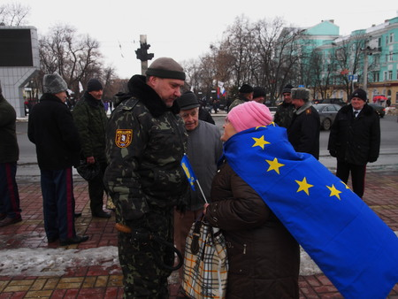 UKRAINE, LUGANS - FEBRUARY 9, 2013  An activist with the EU flag on his shoulders with a Cossack discusses guarding rally Opposition rally in the center of Lugansk near the monument of Ukranian peoet Taras Shevchenko