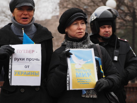 anti war: UKRAINE, LUGANSK - March 2, 2014  woman activist holding posters with texts -  Putler hands off Ukraine  and  Only peace   Protesters rally in Lugansk urging Russia not to interfere in the affairs of Ukraine and other countries to send troops to the count