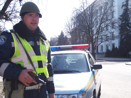 named person: UKRAINE, LUGANSK -  March 6, 2014: An armed traffic officer. In Lugansk it is life as normal, with people walking with children and buying products in the market. But, very near the government buildings are heavily guarded by police.  Editorial