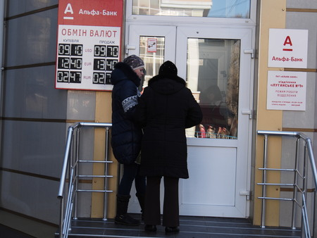 UKRAINE, LUGANSK -  March 6, 2014:Two girls are on the verge of Alfa Bank, to the left, indicating the scoreboard currency prices. Today the U.S. dollar is worth 9.70 hryvnia, a few days ago its price exceeded 11.00 hryvnia