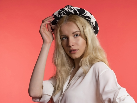 keep an eye on: young blonde hair woman in hat on red background