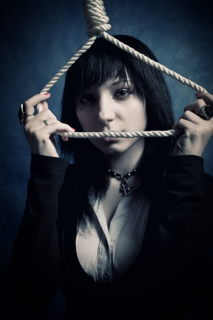 gallow: pretty gothic girl seeing to the camera through the loop over dark