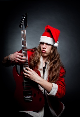Santa posing with electric guitar over dark background Stock Photo - 12087773