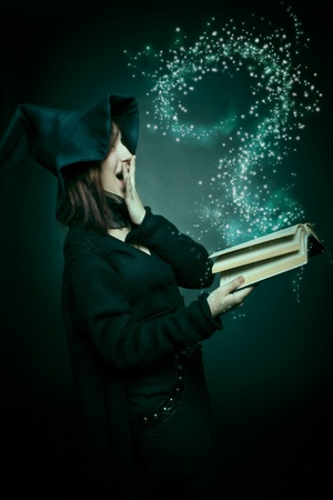 Pretty witch with magic book posing over dark background.