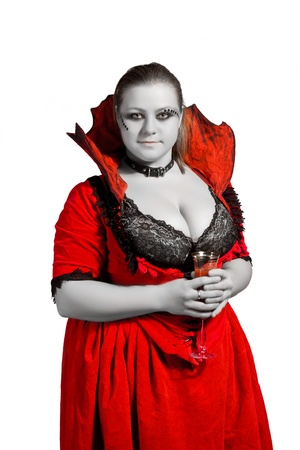Sexy pretty vampire with glass full of blood posing over white Stock Photo - 12086775
