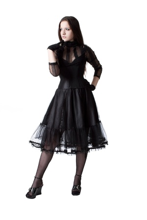 Pretty gothic girl in black dress posing over white photo