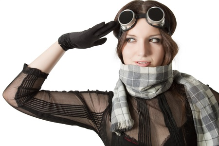 Prety pilot in scarf and googles saluting over white photo