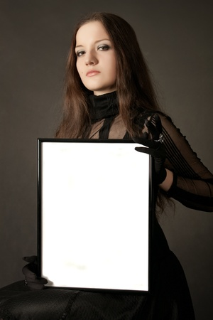 Pretty gothic girl in black dress with blank frame in hands over gray background