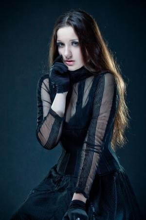Pretty gothic girl posing over dark 스톡 콘텐츠