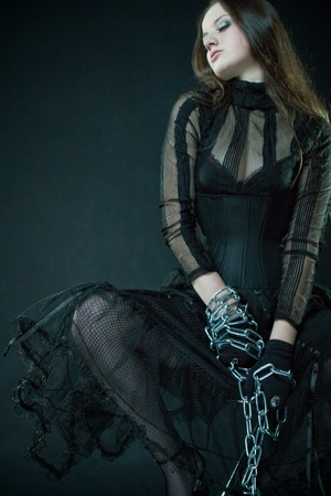 Pretty prisoner in corset bounded by chains over dark 写真素材