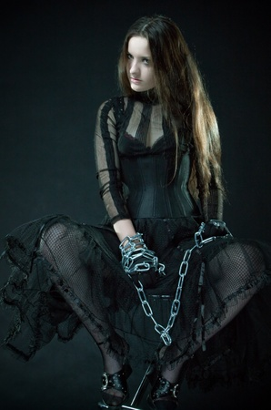 Pretty prisoner bounded by chains over dark Stock Photo - 12148485