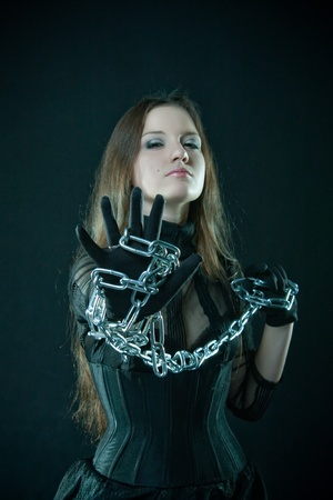 woman prison: Pretty prisoner posing with chains over dark Stock Photo